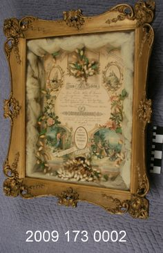 Framed rectangular shadow box holds marriage certificate at back, wedding veil tulle and wax orange blossoms at perimeter. Certificate is printed in German with hand written names filled in. (1896) Missouri History Museum