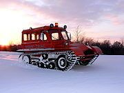 Snowcat - an enclosed-cab, truck-sized, fully tracked vehicle optimized for a snow surface, or soft grounds such as that of a peat bog. In addition to grooming snow they are used for polar expeditions, logging in marsh areas, leveling sugar beet piles, and seismic studies in the wild.