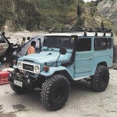 Light Blue Toyota Land Cruiser BJ44 on Beach with Snorkel, Roof Rack, Winch, and Hi-Lift Jack
