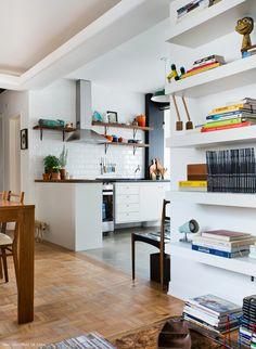 Cozinha integrada com a sala tem piso de cimento queimado e bancada de granito preto.