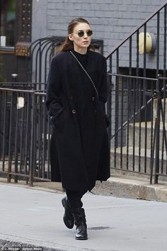 Back to black: The actress went for a long coat and heavy winter boots...