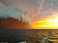 The towering red dust storm is pictured rolling across the ocean as it approaches Onslow in West Australia