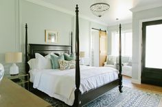 A stunning four poster bed in black adds lovely contrast to the soft gray walls and white linens in this master suite. Throw pillows add a pop of color to the bed, and a bright sitting area with two armchairs offers a place to relax and read a book or two.