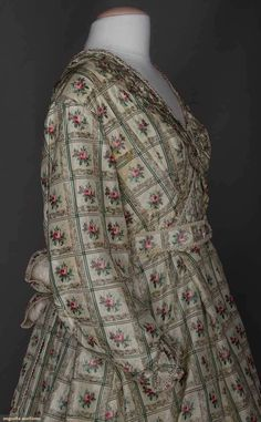 """1-piece printed cream silk taffeta in windowpane pattern w/ chine rosebud centers, ruched self fabric trim, entirely lined in cream cotton, CB skirt cartridge pleated, B 38"""", W 34"""", L 57-75"""", includes 1 boned evening bodice & waistband, (originally 2-piece dress, skirt pleats let out in front, bodice attached to skirt for maternity wear, underarm & skirt stains) fair. Sargeant Family, Boston, MA."""