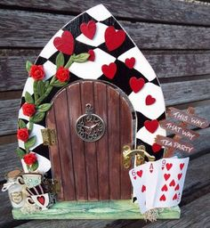 Alice in Wonderland-themed, hand-painted, wooden, hinged fairy door. Complete with red roses and hearts, playing cards and teacups and even a Drink Me potion - but please do not drink it!!!! All our fairy doors are hand-painted, given a shabby chic worn effect on the edges before being varnished and embellishments added. Please PM me to discuss your customised fairy door and colour choices. Other listings for other themed doors will be available soon, in the meantime feel free to pop me a…