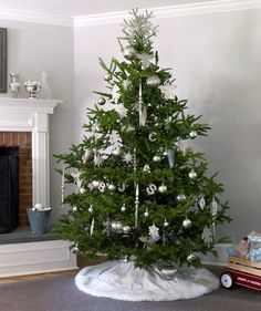 A sophisticated tree decorated with silver ornaments and white lights.