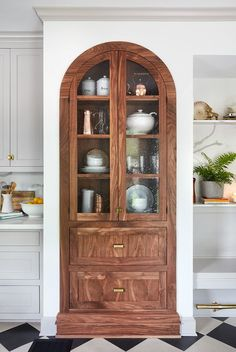 This built-in walnut cabinet really captures your attention when you step into this kitchen. I love that it looks like an original element that's been refinished, rather than something that's been added. Because the kitchen has very limited countertop space, this is the perfect place to store odds and ends that the family still want on display.