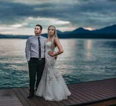 dramatic evening Bride and groom wedding sunset portrait on the dock on Lake Pend Oreille with cloudy skies and mountains photo by Matt Shumate Photography