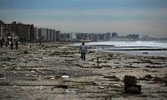 33)  A man walks along the beach in the heavily damaged Rockaway neighborhood, in Queens where a large section of the iconic boardwalk was washed away, on November 2, 2012. (Spencer Platt/Getty Images)