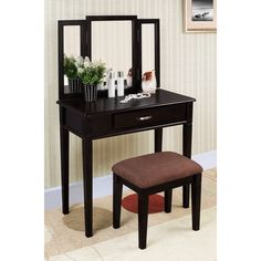 This three-piece vanity set with a black finish is a great addition to your bedroom or bathroom. A tri-folding mirror, table with drawer and upholstered stool finishes this vanity set.