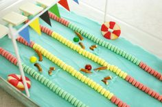 Olympic Swimming Pool Cake made with Candy Necklaces, Sixlets, and Peach Gummy Rings. Swimming Cake, Swimming Pools, Indoor Swimming, Cupcakes, Cupcake Cakes, Swim Team Party, Catering, Olympic Swimming, Fancy Cakes
