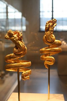Pair of gold armbands  Greek ca, 200 B.C.  These imposing armbands represent two tritons, male and female, each holding a small winged Eros. The hoops behind the Tritons heads are used to attach the armbands to the sleeves of a garment, for otherwise, their weight (each pver 6 1/2 ounces) would have caused them to slip down the arms.