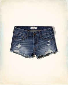 Classic low rise denim shorts in dark washed denim with fading and whiskering, featuring hand-done destruction, frayed cuffs and a five-pocket styling