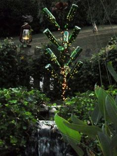 String of lights inserted in bottles on bottle tree for dazzling bottle tree at night Annie Steen 2