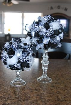 DIY black, white, and silver poms on Dollar Store candlesticks. Use styrofoam balls on top (cut a slice from bottom of ball for better balance?) and stick pins to secure ribbons. Very pretty!