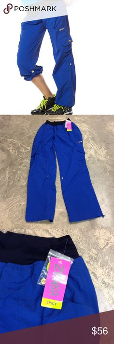 "ZUMBA "" A Cut Above Cargo Pant"" Workout Pants Y13 🔥🔥These size small workout pants are by ZUMBA! They are full length or can roll up into capris via snap tabs! The back zippered pockets have a rainbow tassel for flare while you move! ***BRAND NEW WITH TAGS :) Zumba Fitness Pants Track Pants & Joggers"