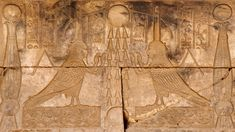 """Two images of the soul (ba) of Osiris in the form of a human headed bird decorate the court of the eastern Osiris chapels on the roof of the Hathor Temple at Dendera. The heads are topped by absurdly big """"perfume cones"""". The birds are placed on either side of three sun rays which connect a sun up in the sky and another one which is sitting on the horizon.  This part of the Dendera Temple was built during the later Ptolemaic period (first century BC)."""
