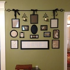 Gallery wall from various old picture frames painted black, curtain rod & black ribbon, dollar tree serving trays painted black, and scrapbook paper. And it hides the thermostat too! Just add the photos!