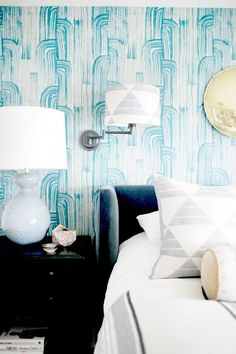 Bedroom with blue wallpaper, a printed sconce, and a bedside lamp