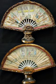 """1760-90. Double-sided fan, """"At the Couturier.""""  Painted paper leaf, on sticks of mother-of-pearl accented with mica on the guards.  France.  Many elegant ladies are shopping at the couturiere's, while many interested gentlemen admire them through the front shop windows.  Very unusual:  the windowpanes are fine translucent silk, so that silhouettes of the painted details stand out when the fan is held up to the light."""