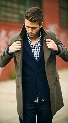 jeans, a navy tweed jacket, a plaid shirt and an olive green coat over