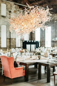 Wedding reception in an industrial space with a large chandelier, and a vintage velvet armchair