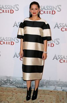 Golden girl: Marion Cotillard, 41, shielded her blossoming baby bump with an effortlessly chic striped dress as she attended a photo call for Assassin's Creed in Paris, France on Monday