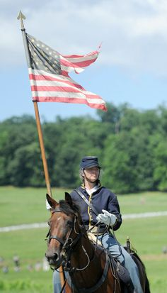 A reenactor portraying a soldier takes a lap around the field to greet the visitors at the Hanover cavalry battle during the Blue Gray Alliance reenactment in Gettysburg, Pa.
