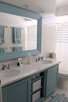 Soothing blue bathroom with white. Love the open cabinet underneath with baskets. Farmhouse/Country feel for me.