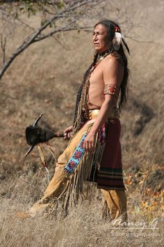 A Native American Indian man standing with a weapon with horns