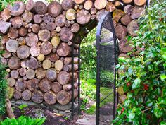 Woodpile Gate in cordwood wall\/fence at Sakonnet Garden in Little Compton, Rhode Island. Stacking Firewood, Log Fence, Little Compton, Wood Waste, Log Wall, Gothic Garden, Wood Creations, Garden Fencing, Garden Projects