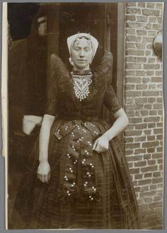 Vrouw in Axelse streekdracht. De vrouw is gekleed in de zondagse dracht. Ze draagt over de ondermuts en het oorijzer een 'trekmuts'. Aan de 'krullen' (oorijzeruiteinden) van het oorijzer hangen 'dubbele strikken' (dubbele, klaverbladvormige gouden oorijzerhangers). Een opvallend onderdeel van de Axelse vrouwendracht is de hoog opgespelde schouderdoek, welke met papier verstevigd wordt. #Zeeland #Axel