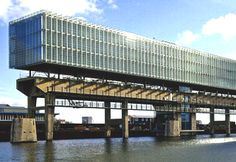 Kraanspoor Office Building  Spanning an abandoned craneway, this ingenious structure is the office of the architectural firm Ontwerpgroep Trude Hooykass. The 3 story concrete, steel and glass structure 270m by 14m wide is perched atop the 3m high concrete beams of the industrial frame of the older craneway.