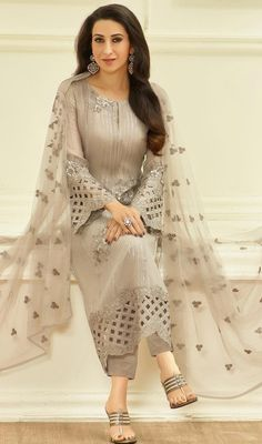 You will be the center of attention like Karisma Kapoor in this beige color embroidered georgette pant style suit. The ethnic lace, sequins and resham work in the attire adds a sign of elegance statement to your look. #georgettesuits #straightcutdress #anklelengthdresses