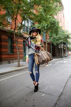 striped tee + distressed skinny jeans + black ankle boots + black fedora + Louis Vuitton duffle bag