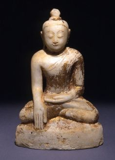Gotama Buddha in the gesture of Enlightenment. This image shows the Buddha on the night of his awakening. When challenged by Mara, he demonstrates his worthiness to become enlightened by touching the ground and calling the Earth Goddess to witness his good deeds. Mara flees before the evidence, leaving the Buddha-to-be to become the enlightened Gotama at dawn. 1700s, Burma (Myanmar). Marble with lacquer and gilding. 1872,0701.11. Donated by the Bridge Family.