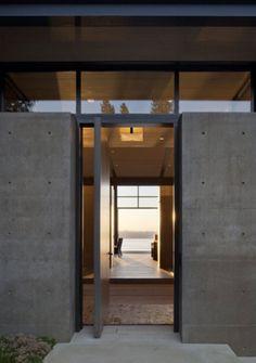 solid black pivot entry door and cement facade. Very nice industrial look