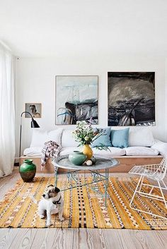 Art on the walls, green vase, yellow geometric rug and little dog
