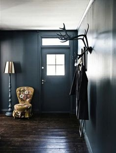 Dark grey walls. Floral chair. Interesting wall display. Love.