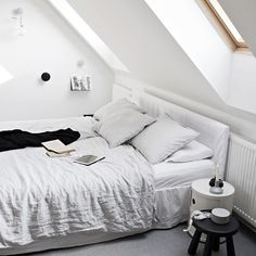 Cozy monochrome attic bedroom. That soft grey linen blanket looks so inviting...