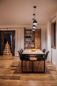 Duży drewniany stół stanowi centralny punkt w jadalnianej strefie. Przy czarnych krzesłach czy lampach wiszących dodatkowo zyskuje na wyrazie. Nowoczesny minimalizm nie umniejsza eleganckiej strony aranżacji.