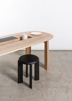Miro Dining Table is a minimal table by Studio Snng that's a nod to Joan Miro's curved shapes with a hidden lid transforming into a trivet when flipped.