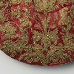 Half round, flat pouch ceriserood satin embroidered with symmetrical floral and leaf motif in gold thread, with drawstring and silk tassels, anonymous, ca 1600 - ca 1699    Silk, gold leaf, flossing l 10.5 cm × W 15cm.