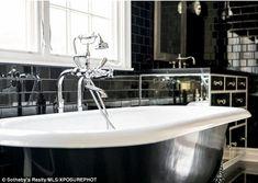 Scrub a dub dub: Kylie'sparticularly lavish bathroom is clad in black tiles with a clawfo...