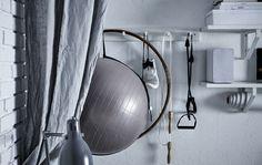 Detalhe de parede com equipamento de exercício físico pendurado em ganchos e prateleiras com caixas e uma coluna.