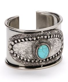 Master the task of luxe accessorizing with this sleek silver cuff. Flaunting a classic turquoise stone set in intricate metal casting, it's the perfect finish to any chic ensemble.