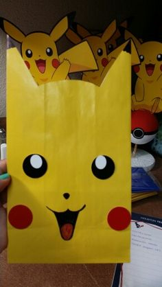 """Pokémon party candy bags Yellow paper bags (party city) Cheeks and eyes I used an 1"""" circle cutter the mouth and nose I just draw it with a sharpie. And just cut the ears.  You will need tape so you can close after filling it up with candy and it can keep its shape."""