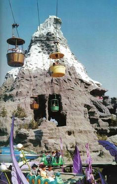 Vintage Disneyland: The Monorail zips past the Matterhorn while pre-1965 Skyway buckets glide through it, as viewed from the Alice in Wonderland elevated track.