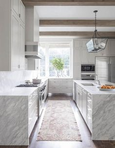 Contemporary white and grey kitchen features gray wash wood ceiling beams over white cabinets paired with grey and white quartzite waterfall edge countertops and quartzite slab backsplashes.