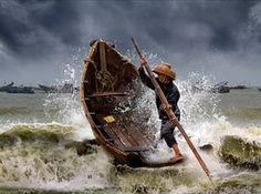 Braving the storm - Dianbai fishing village China, by Joseph Tam 'This shot was taken from a fishing village in Dianbai, in China's Guangdong province. The fisherman in the timber boat is a courier who brings the catches from fishing boats to shore regularly. The swirling threat of the storm clouds and thunderous clamour of the angry waves sends a foreboding message to most.'